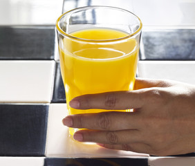 hand with orange juice in sunshine, realistic Atmosphere