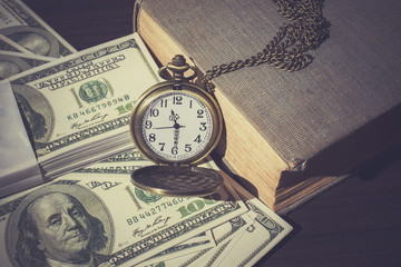 Pocket watch on bills and old book as vintage