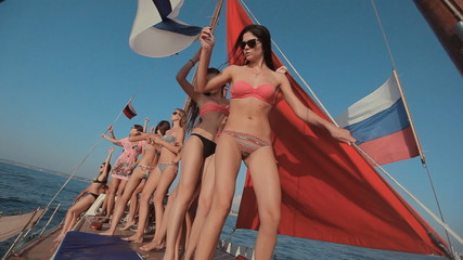 Young girls in bikini relaxing on a yacht with red sails and a