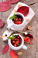 chocolate mousse in a white ceramic cup with pomegranate