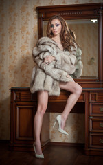 Attractive sexy young woman wearing only a fur coat posing