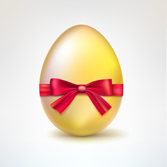 Golden egg with red bow.