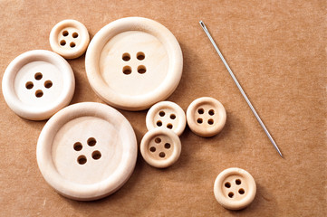Unpolished wooden buttons and needle on brown carton