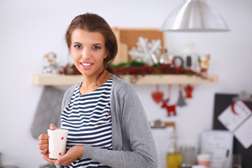Portrait of young woman with cup against kitchen interior