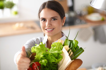 Young woman holding grocery shopping bag with vegetables and