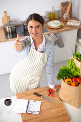 Woman in apron standing on the desk with grocery bagand showing