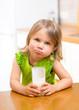 child girl drinking yogurt or milk in kitchen