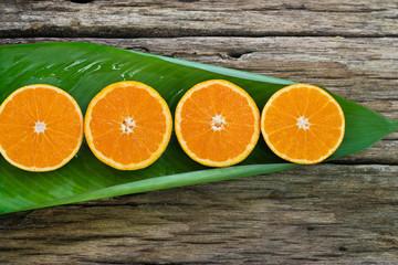 Orange fruit Slices on leaf and wooden background, nature concep