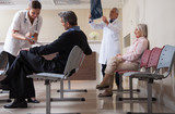 Doctors reviewing x-ray at hospital reception while people sitti