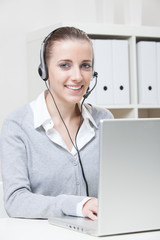 Young smiling business woman with headset
