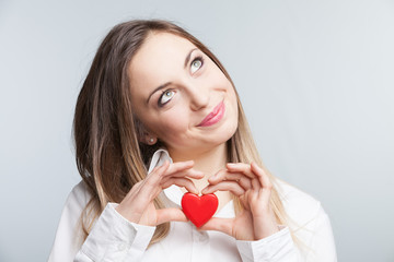 Portrait of a cheerful female holding a heart
