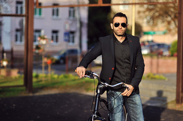 Young stylish man with retro bicycle outdoor