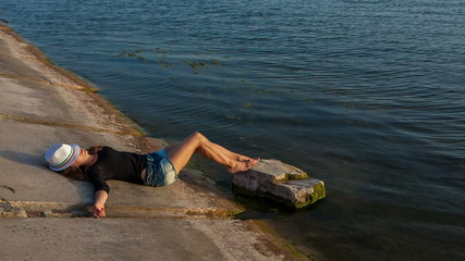 Woman in hat and short shorts lying near the water