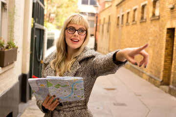 a young woman pointing holding a map