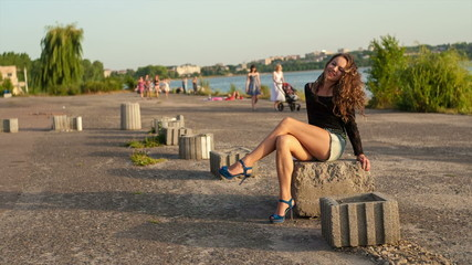 Pretty girl in shorts with long legs sitting on the shore