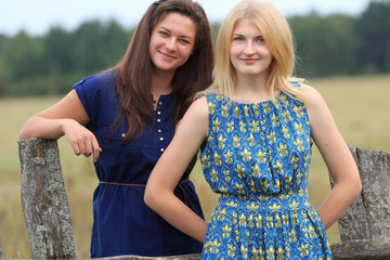 Blonde and brunette girls near old-fashioned fence