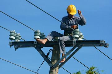 Asian electrician climb high, work on electric pole