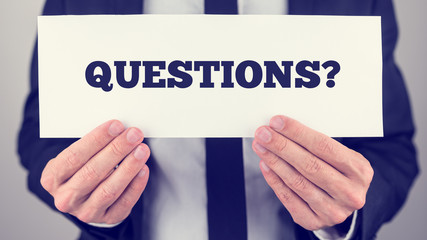 Businessman holding Questions sign towards you