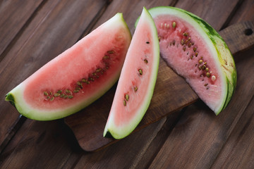 Watermelon slices on a rustic wooden cutting board, close-up