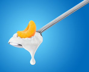 Spoon of peach yogurt on blue background