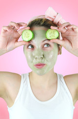 Funny woman wearing a green facial mask and cucumbers.