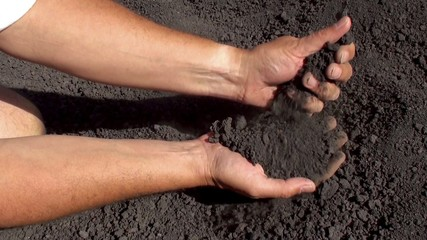 Hands strew a slag lava sand from the mount Etna.