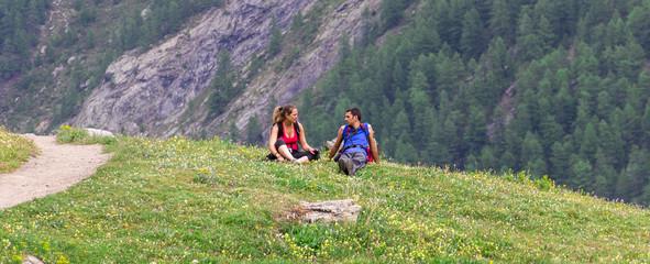 Coppia seduta su prato in montagna