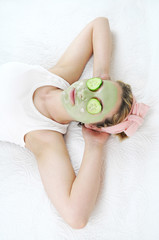 Young woman wearing a green facial mask and cucumbers.