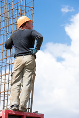 Man worker mounting concrete formwork during construction works