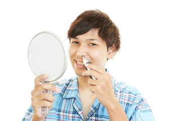 鼻腔のケアをしている男性
