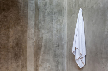 The white towel is hanging on a hanger with concrete wall in the