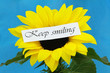 Keep smiling card on sunflower on blue background