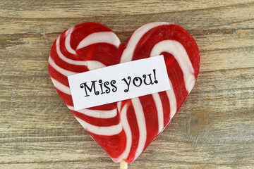 Miss you card with heart shaped lollipop on wooden surface