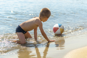 Beautiful boy playing with the beach ball in the sea