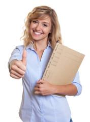 Sekretärin mit blonden Locken zeigt den Daumen