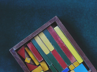 multiple colored toy cubes on wood box on green background