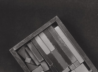 toy cubes on wood box on dark velvet background in monochrome