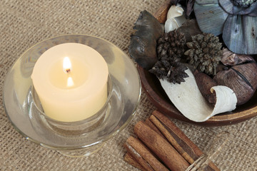Potpourri, candle and cinnamon on burlap background