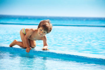 Small boy climbs on boarder of swimming pool