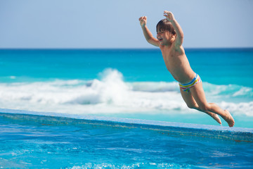 Jumping to the pool excited boy