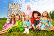 Leinwanddruck Bild - Smiling children in festival costumes sit close
