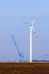 Wind turbine in the field beside crane.
