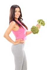 Attractive woman holding a broccoli dumbbell