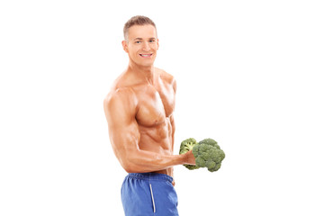 Male bodybuilder holding a broccoli dumbbell