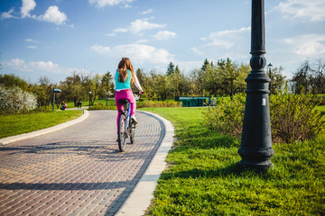 Young woman riding on bicycle in park