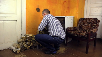 Man carry armful of firewood and put near rural house stove