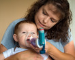 Infant getting breathing treatment from mother