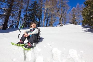 Ragazza seduta su neve con ciaspole