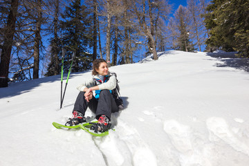 Ragazza con ciaspole seduta su neve