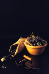 Wine bottle, dark blue grapes and opener